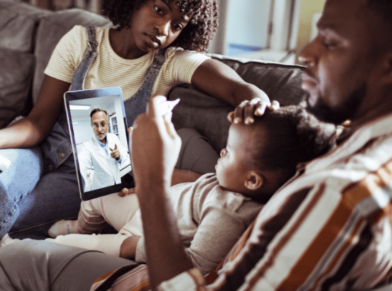 Family on couch with ipad taking with a doctor.
